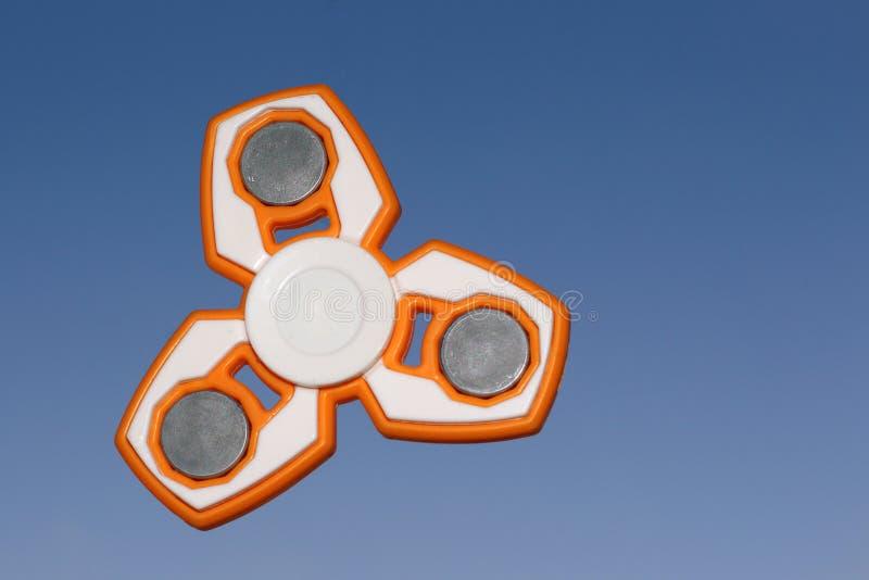 Bianco e giocattolo arancio di alleviamento di sforzo del FILATORE di irrequietezza sulla parte posteriore del cielo immagini stock libere da diritti