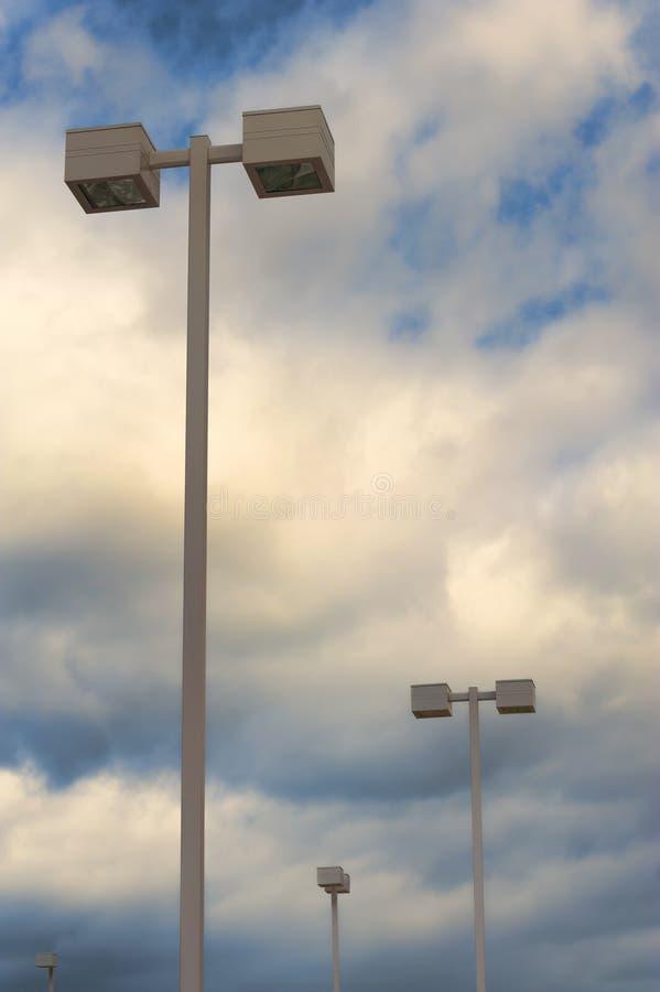 In bianco e nero dei pali leggeri e delle nuvole del parcheggio fotografia stock libera da diritti