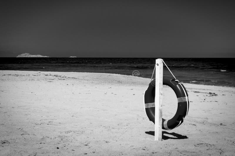 In bianco e nero del salvagente su una spiaggia abbandonata fotografia stock libera da diritti