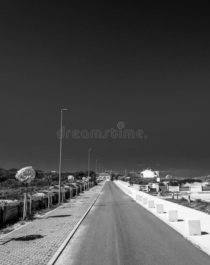 In bianco e nero della strada del deserto vicino alla spiaggia sarda fotografia stock