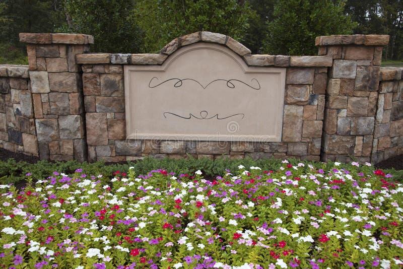 In bianco firmi dentro la parete della roccia circondata dai fiori e dagli alberi immagini stock libere da diritti
