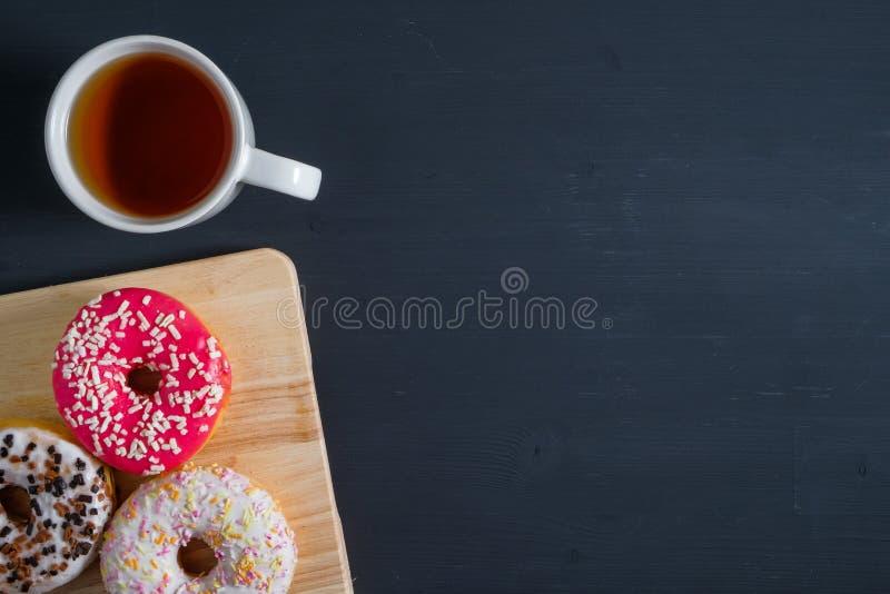 Bianco, rosa e guarnizioni di gomma piuma lustrate marroni con la tazza di t? nella parte di sinistra su fondo di legno nero fotografia stock libera da diritti