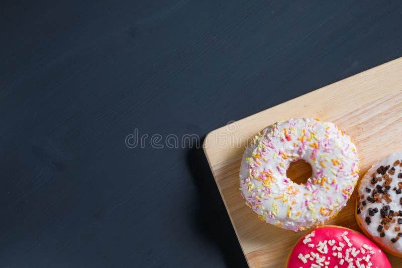 Bianco, rosa e guarnizioni di gomma piuma lustrate marroni nella destra su fondo di legno nero fotografie stock