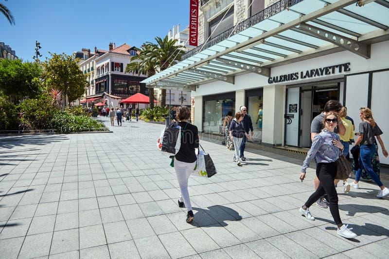 Biarritz, France, femme marchant avec des sacs près des fenêtres de magasin de Galeries Lafayette photographie stock