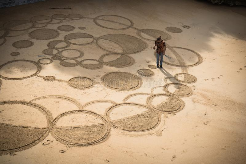 Biarritz, France - October 4, 2017: upper view on man artist creating sand drawing with wooden stick. On sandy beach stock photography