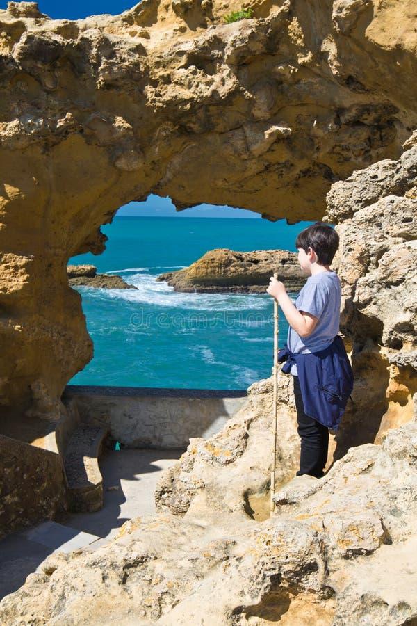 Biarritz, Francia - 20 de mayo de 2017: muchacho joven que mira a través del agujero de la cueva del mar que admira hermosa vista fotos de archivo