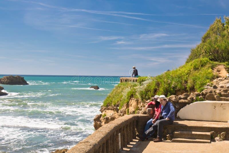 Biarritz, Francia - 20 de mayo de 2017: Pares jovenes que admiran la belleza del paisaje marino en costa atlántica en primavera c fotografía de archivo