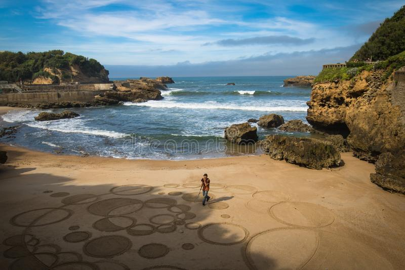 Biarritz, Francia - 4 de octubre de 2017: opinión superior sobre el artista del hombre que crea el dibujo de la arena con el pali fotos de archivo