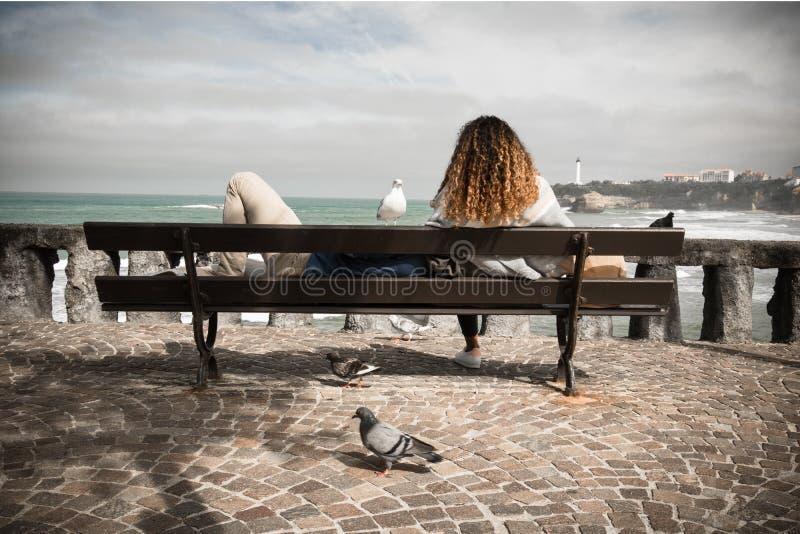 Biarritz, Francia - 4 ottobre 2017: turisti che si rilassano sul banco che guarda l'oceano a Biarritz turistica meravigliosa fotografie stock libere da diritti