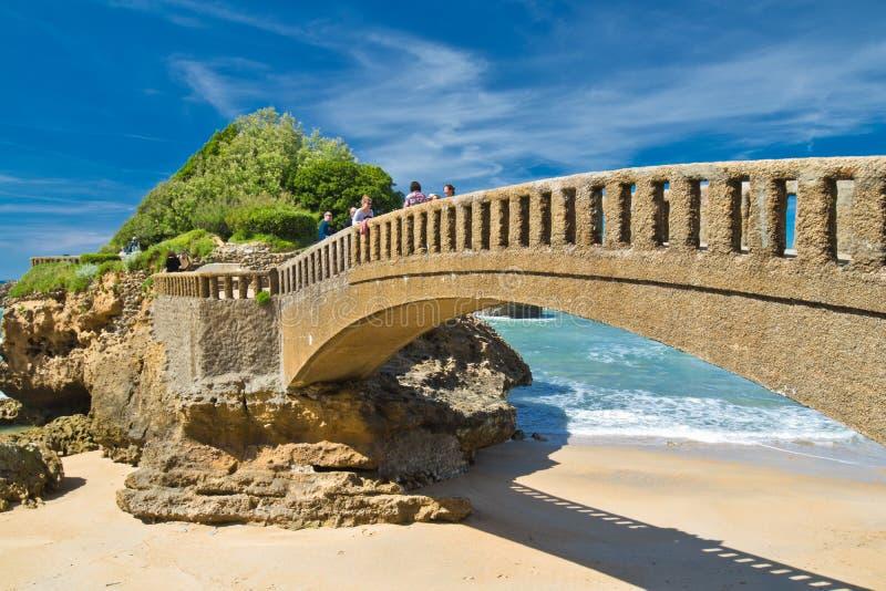 Biarritz, Frankrijk - Mei 20, 2017: mensen die op steenvoetgangersbrug lopen in toneelzeegezicht op Atlantische kustlijn in blauw royalty-vrije stock fotografie