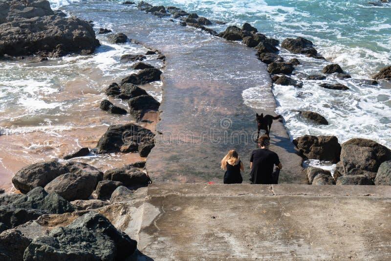 Biarritz, Frankrijk - September 13, 2018: koppel zitting op voetgangersbruggolfbreker aan een hond genietend van mooie mening en  stock foto's