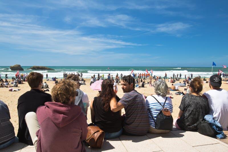 Biarritz Frankrike - Maj 20, 2017: sandig strand mycket av folk som håller ögonen på och tar foto av surfareisa-världen som surfa royaltyfria foton