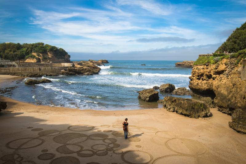 Biarritz Frankrike - Oktober 4, 2017: övresikt på mankonstnären som skapar sandteckningen med träpinnen royaltyfri foto
