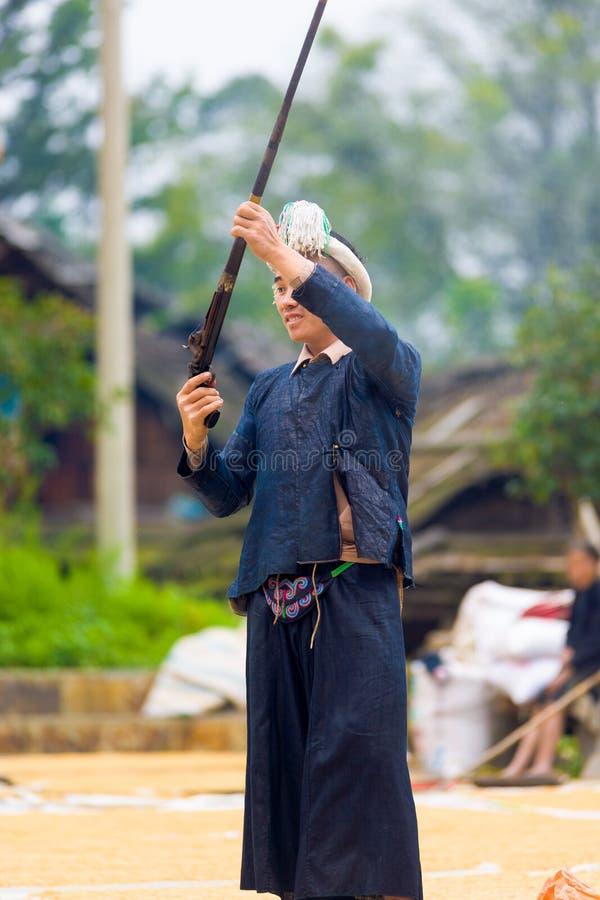 Biasha Miao Minority Man Shooting Gun Hair Bun. Biasha, China - September 17, 2007: Miao ethnic minority man in traditional blue clothes, braided headdress and stock images