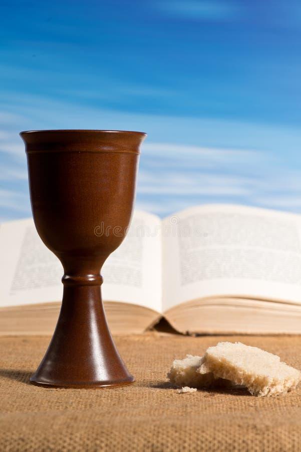 Bibbia aperta con il calice di vino immagine stock