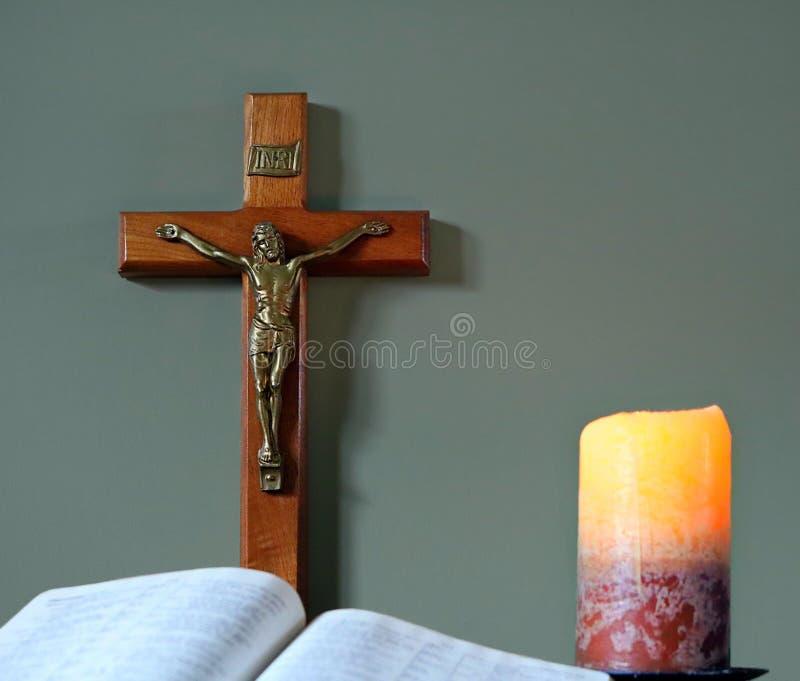 Bibbia aperta con la croce e la candela accesa fotografia stock libera da diritti