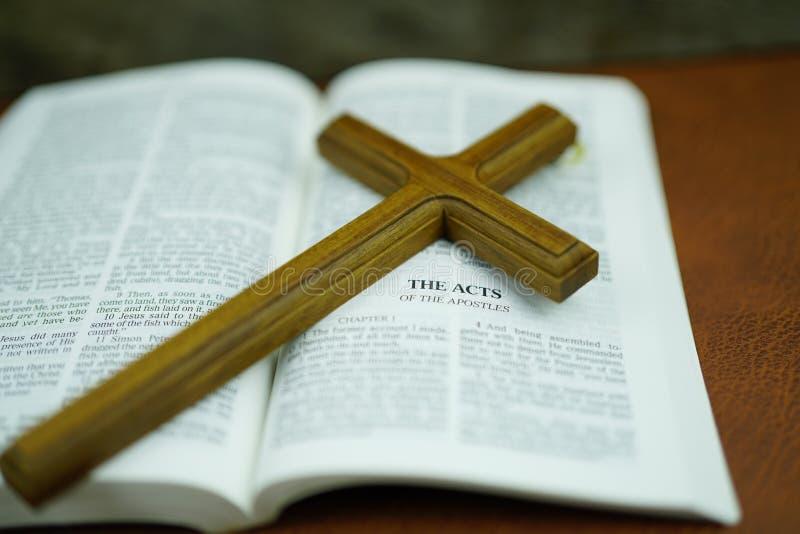 Bibbia con l'incrocio santo di defocus sulla tavola di cuoio Fuoco selettivo fotografia stock