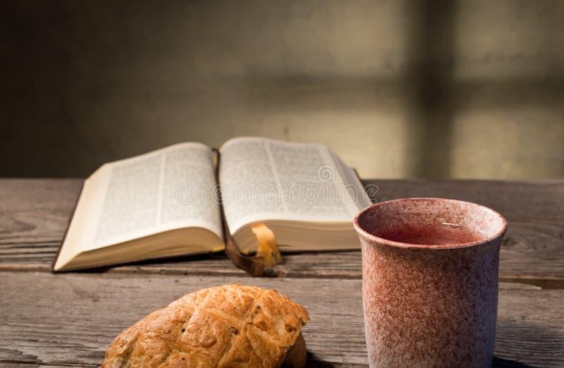 Bibbia con pane ed il calice fotografia stock