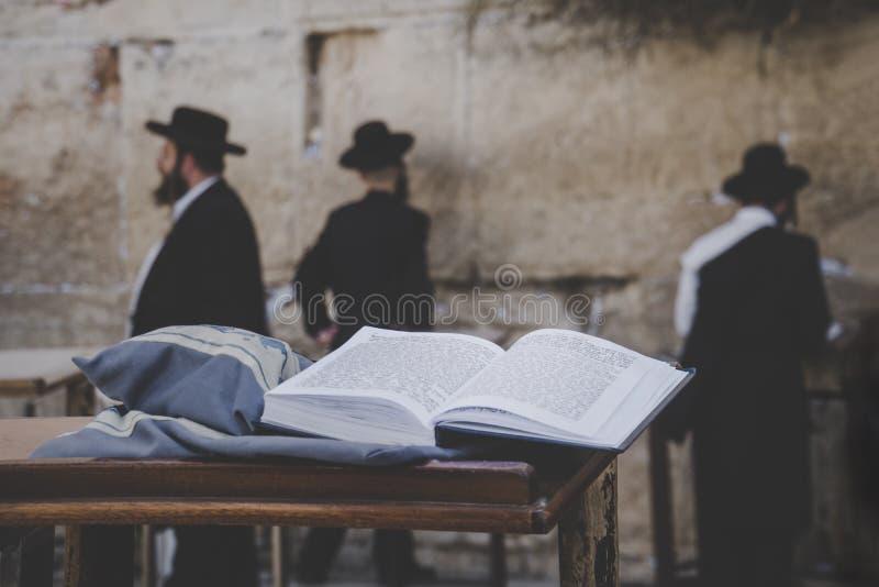 Bibbia ebrea - Torrah sulla tavola su fondo vago degli ebrei pregare e della parete occidentale lamentantesi l'israele gerusalemm fotografia stock libera da diritti