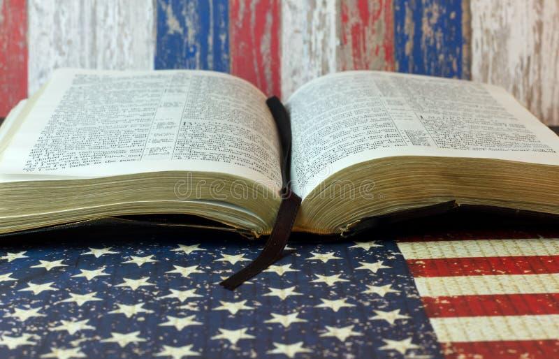 Bibbia santa contro una bandiera americana immagini stock libere da diritti