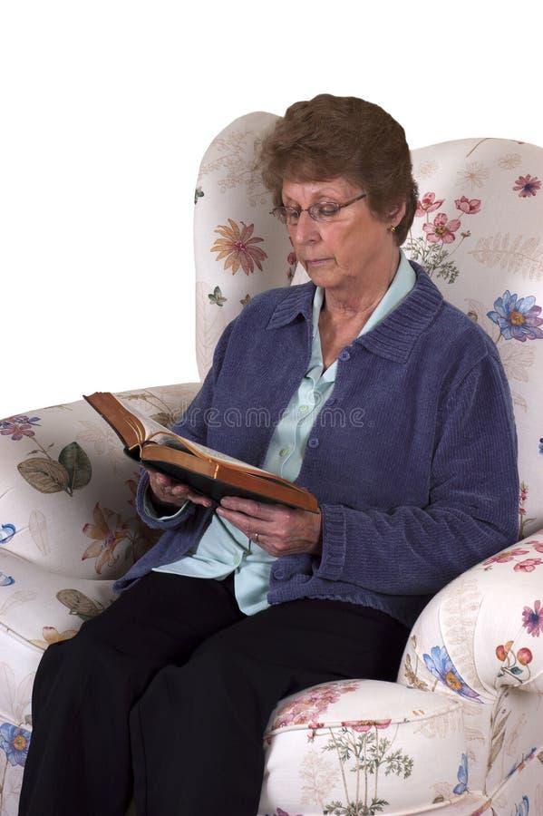 Bibbia santa di Readin della donna maggiore matura cristiana fotografie stock