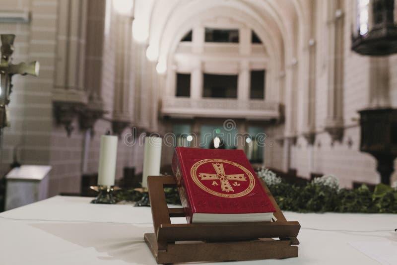 Bibbia santa sulla tavola durante la massa nuziale di cerimonia di nozze Concetto di religione Ornamenti cattolici del eucharist  immagine stock