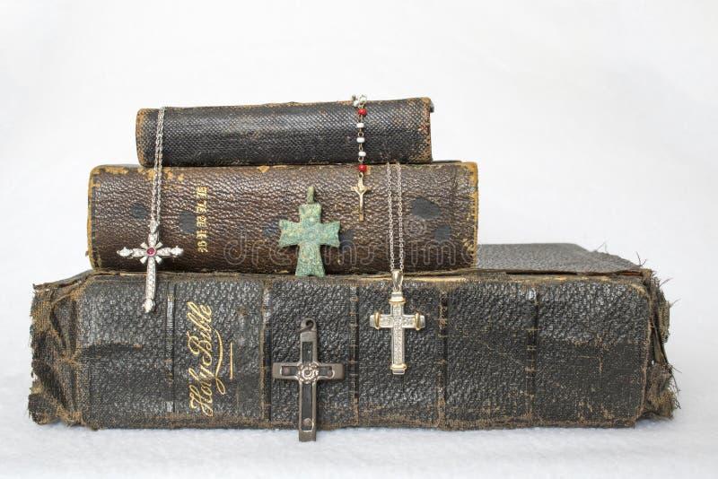 Bibbie di cuoio indossate antiche con l'oggetto d'antiquariato agli incroci moderni su Wh fotografia stock