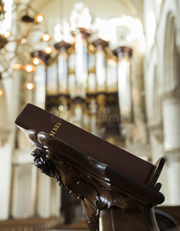 Bibel in a church in holland. Bible on the pulpit in achurch in holland with an organ in the background royalty free stock photo