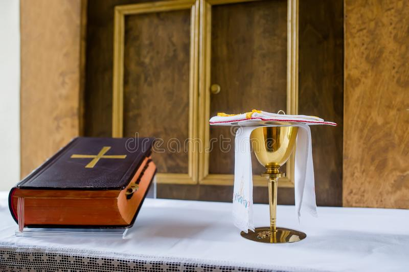 Bibel med korset på tabellen som är klar för bön i horisontalriktning Bred vinkel Lens som täckas av det Lens locket i mitt royaltyfri bild