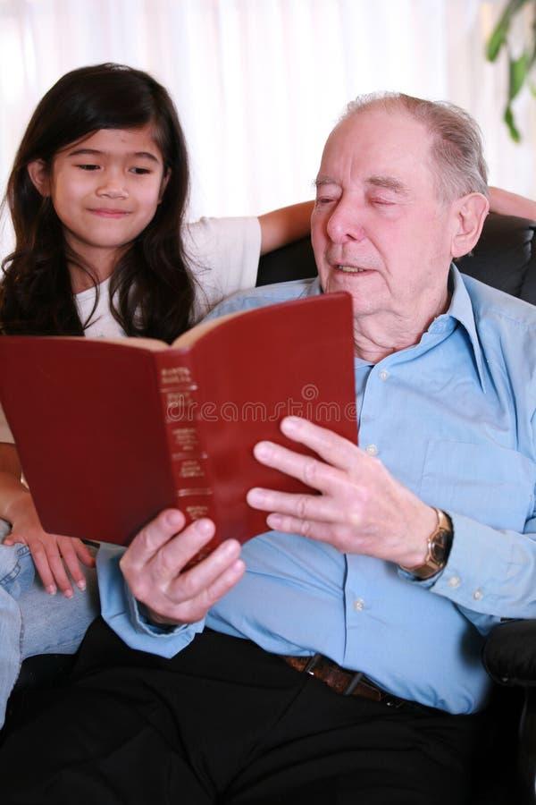 Bibel Messwert des älteren Mannes und des kleinen Mädchens zusammen lizenzfreie stockfotos