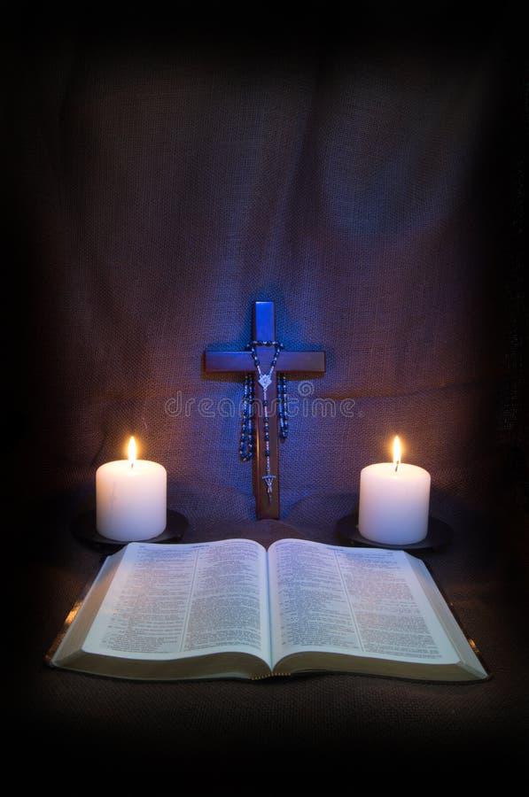 Bibel, Rosenbeet, Kruzifix und zwei Kerzen stockbild