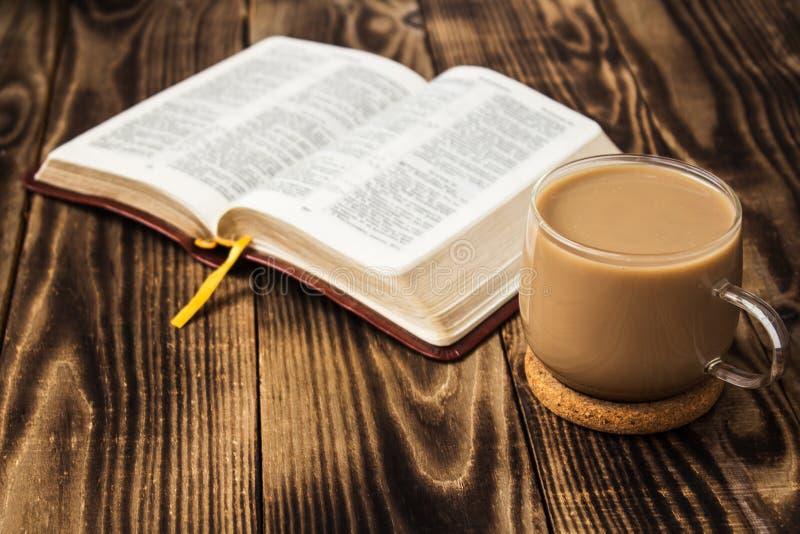 Bibeln och kaffe med mjölkar på träbakgrund royaltyfri foto