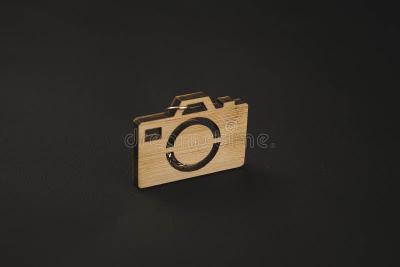Bibelot en bois sous forme de caméra sur un fond noir Keychain image stock