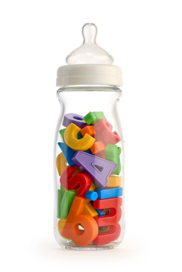 Biberón aislado que contiene letras coloridas del juguete fotografía de archivo libre de regalías