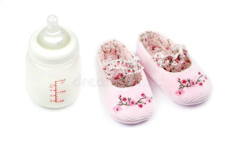 Biberon et chaussures de bébé roses photos stock