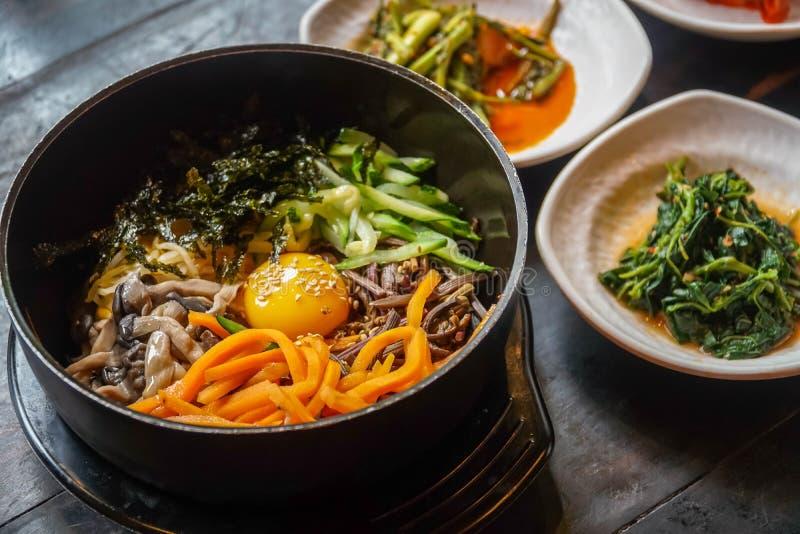 Bibimbap coreano tradicional del plato servido junto con los pequeños acompañamientos Clled Banchan Cocina auténtica asiática foto de archivo