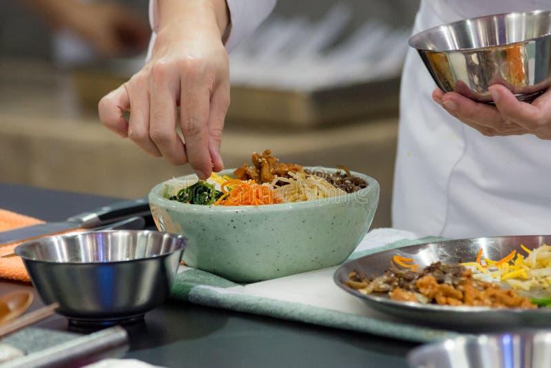 Bibimbap, Traditional Korean cuisine bibimbap, Chef preparing Korean food, chef cooking in kitchen royalty free stock photos