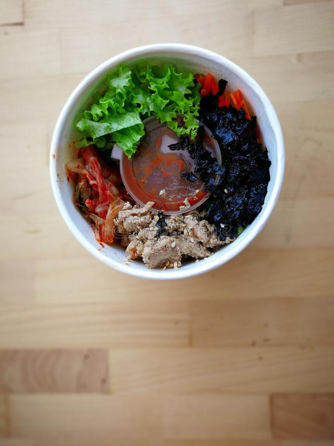 Bibimbap, traditional Korean dish in a take away box, rice with vegetables and beef. stock image