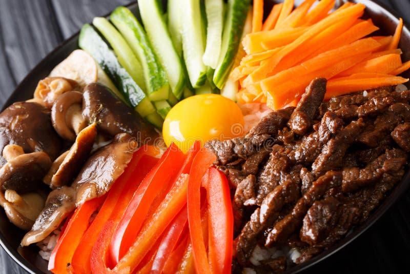 Bibimbap z wołowiną, yolk, warzywami, pieczarkami i ryż makro-, fotografia stock