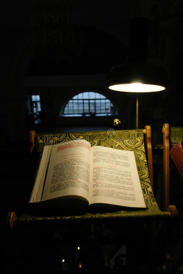 The Bible. A bible on a stand in the light of a lamp stock photography