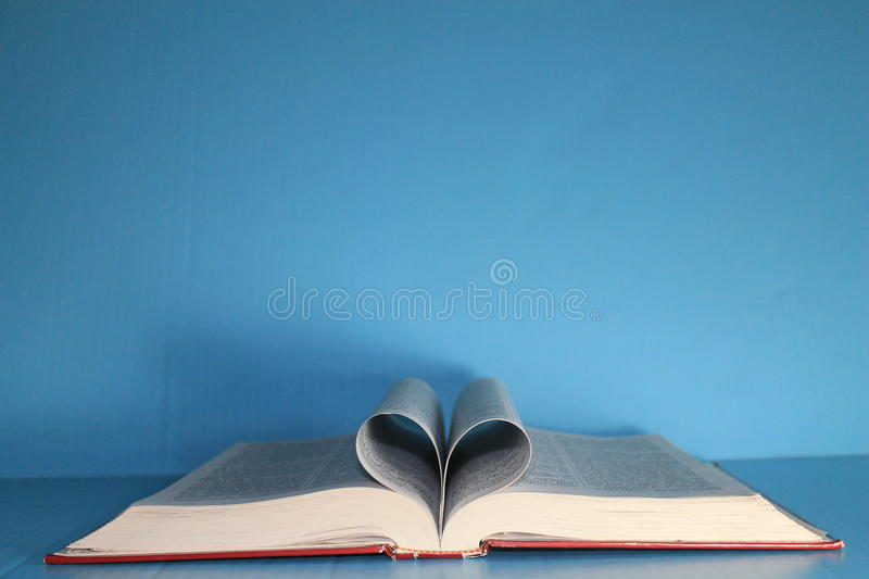 Download Bible On Blue Poster Board With Pages Folded Into Heart Shape Stock Image
