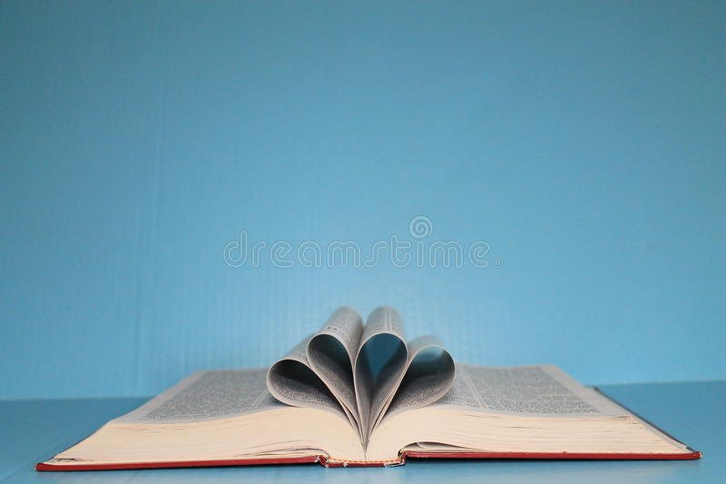 Download Bible On Blue Poster Board With Pages Folded Into 2 Heart Shapes Stock Image
