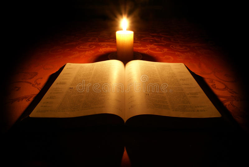 Bible and candle. Open bible with burning candle royalty free stock photography