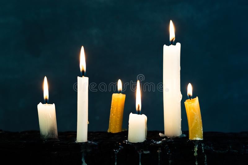 Candles on an old wooden burnt table. Beautiful dark background. Religious concept. royalty free stock image