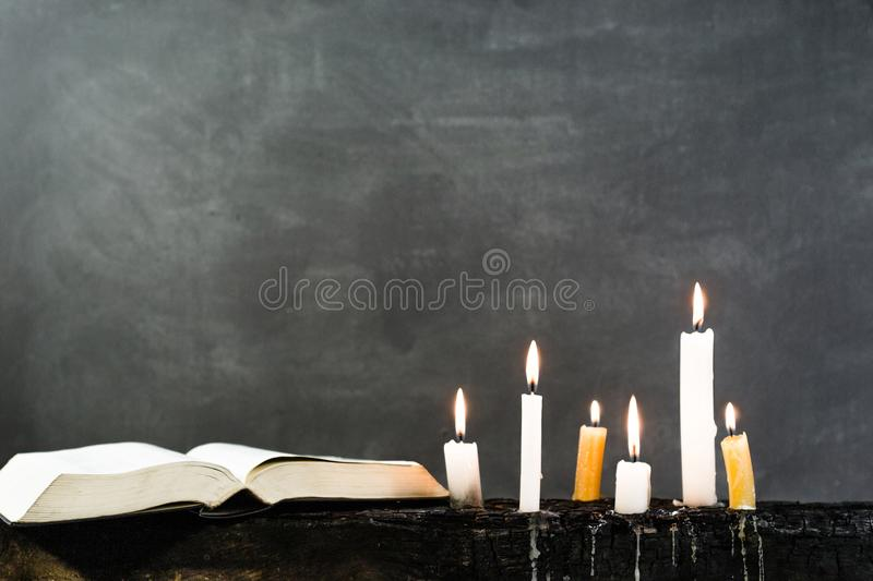 Candles on an old wooden burnt table. Beautiful dark background. Religious concept. stock image