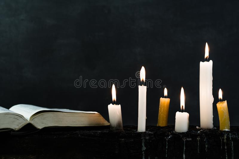 Candles on an old wooden burnt table. Beautiful dark background. Religious concept. stock photos