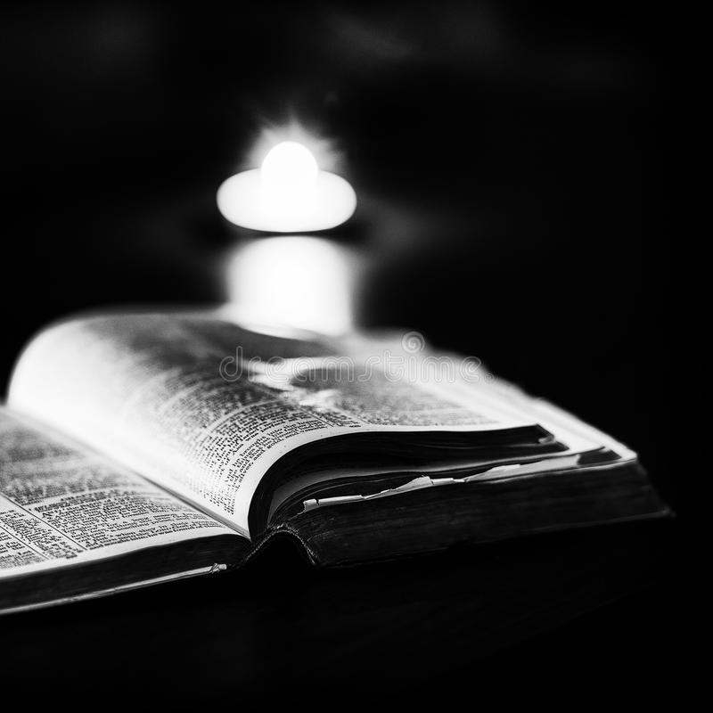 Bible with candles. In the background. Low light high contrast black and white image stock images