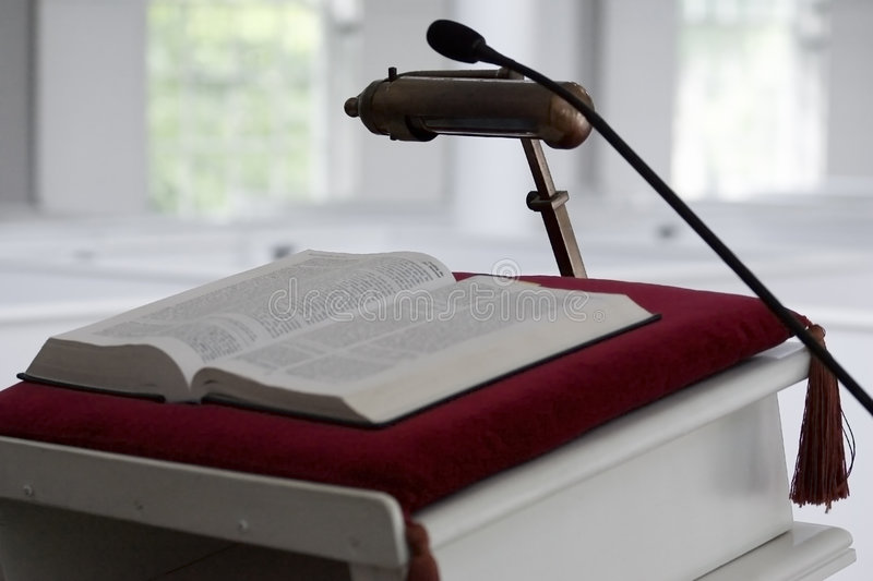 Bible On Church Pulpit. An open Bible on crimson cushion on a church pulpit