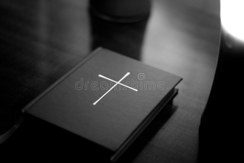Bible with cross. Black and white photo of The Book of Common Prayer (a collection of traditional Christian Anglican liturgy) lit by candles royalty free stock photo
