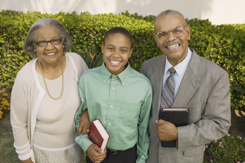 Bible de fixation chrétienne de parents et de fils photo stock